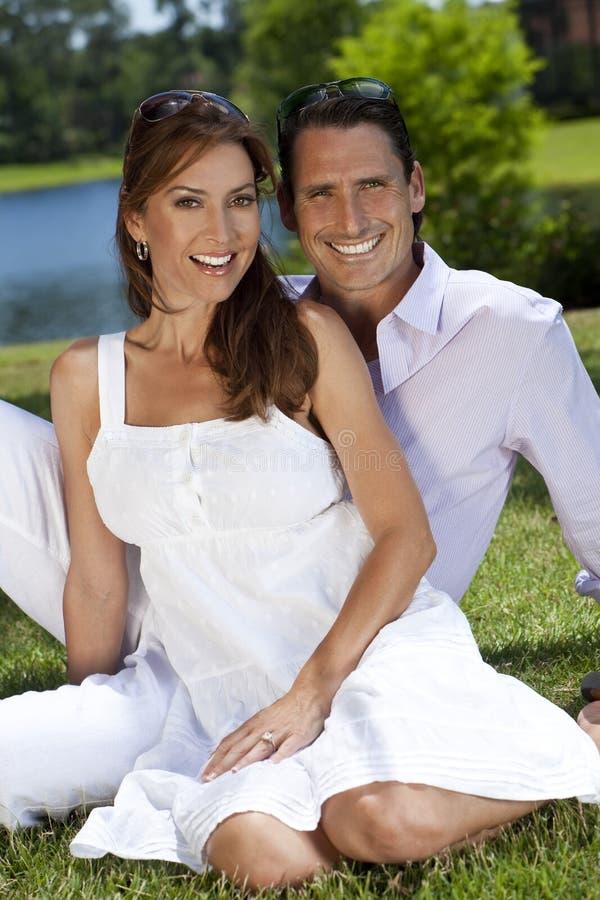 Coppie felici della donna e dell'uomo che si siedono all'esterno fotografia stock