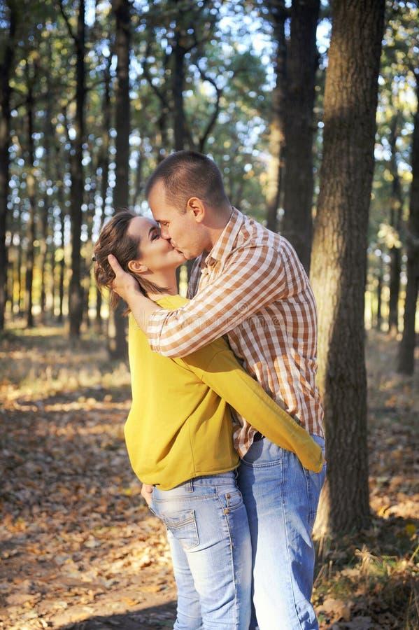 Coppie felici di amore che camminano nella foresta e che baciano, giovani coppie romantiche adulte, abbigliamento casual immagine stock libera da diritti