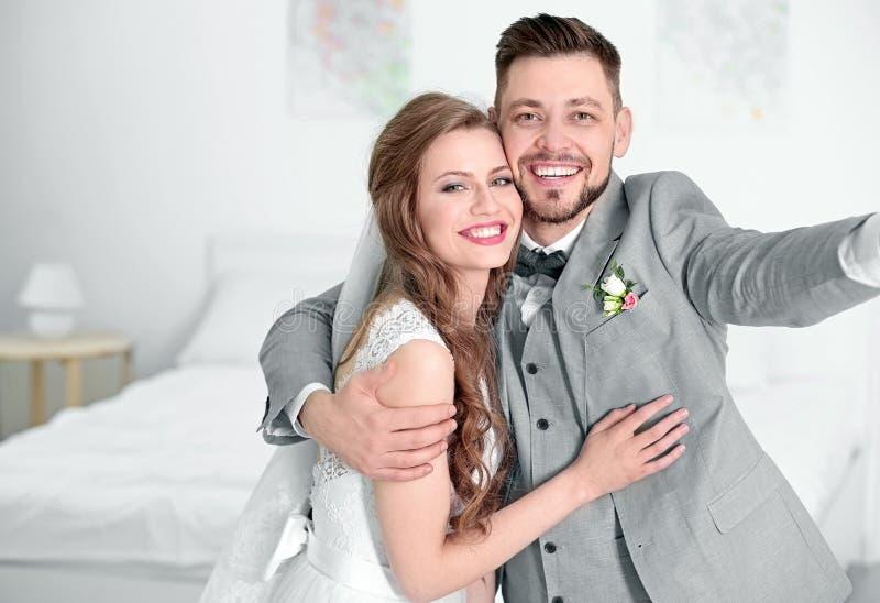 Coppie felici di nozze che prendono selfie fotografie stock