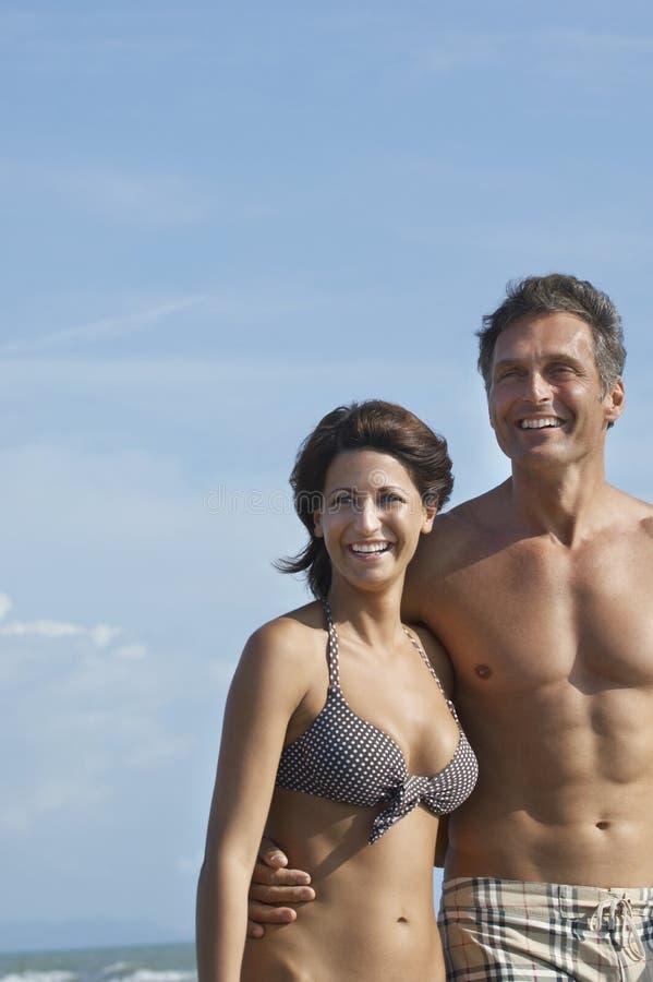 Coppie felici di Semidressed contro il cielo sulla spiaggia fotografia stock