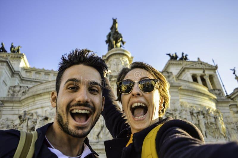 Coppie felici di viaggio che prendono selfie con lo smartphone in punto di riferimento famoso nella piazza Venezia, Roma, Italia  fotografia stock libera da diritti
