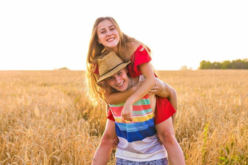 Coppie felici divertendosi all'aperto sul giacimento di grano sopra il tramonto Famiglia allegra di risata insieme Concetto di li immagine stock