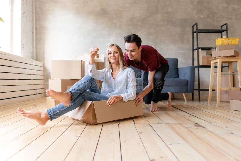 Coppie felici divertendosi e guidando in scatole di cartone a nuova casa Giovani coppie che avvicinano verso un nuovo appartament fotografia stock libera da diritti
