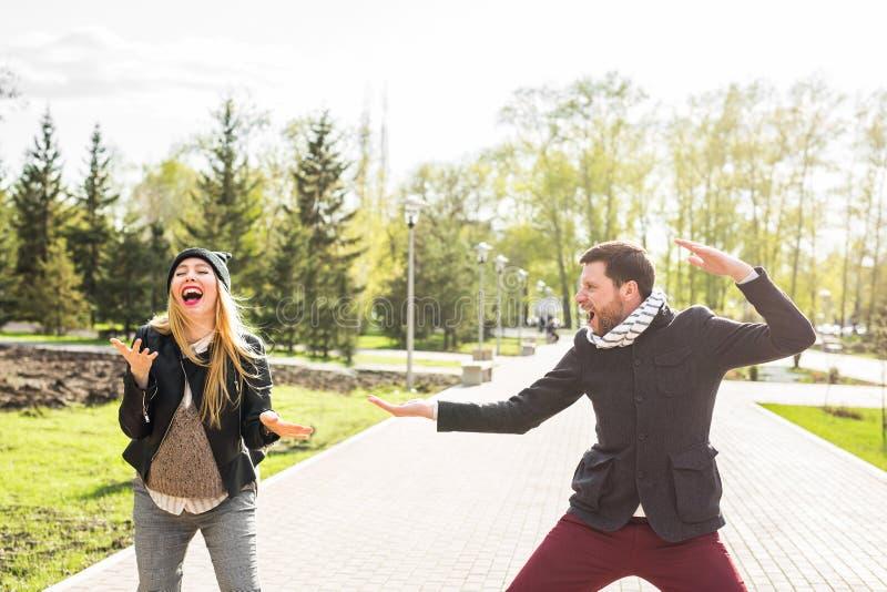 Coppie felici divertendosi ed imbrogliando intorno L'uomo allegro con la donna ha tempo piacevole Buona relazione immagine stock