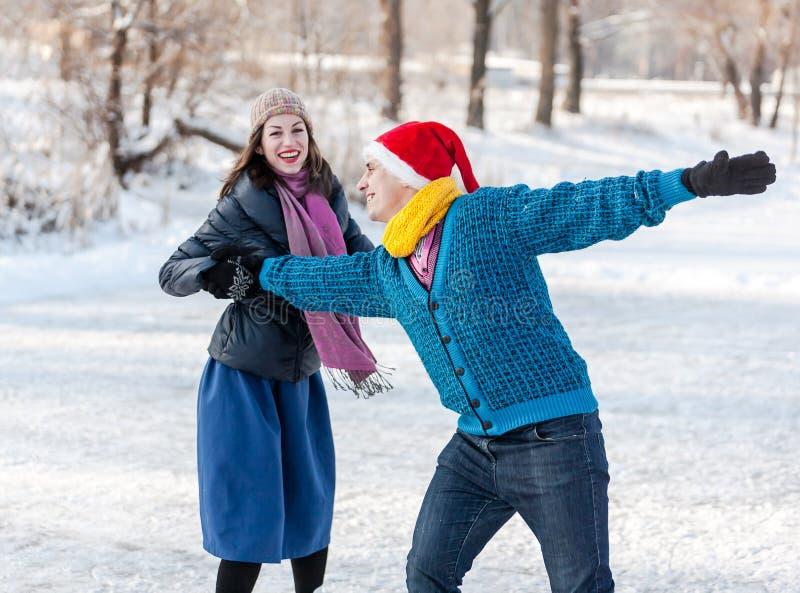 Coppie felici divertendosi pattinaggio su ghiaccio sulla pista di pattinaggio all'aperto fotografie stock