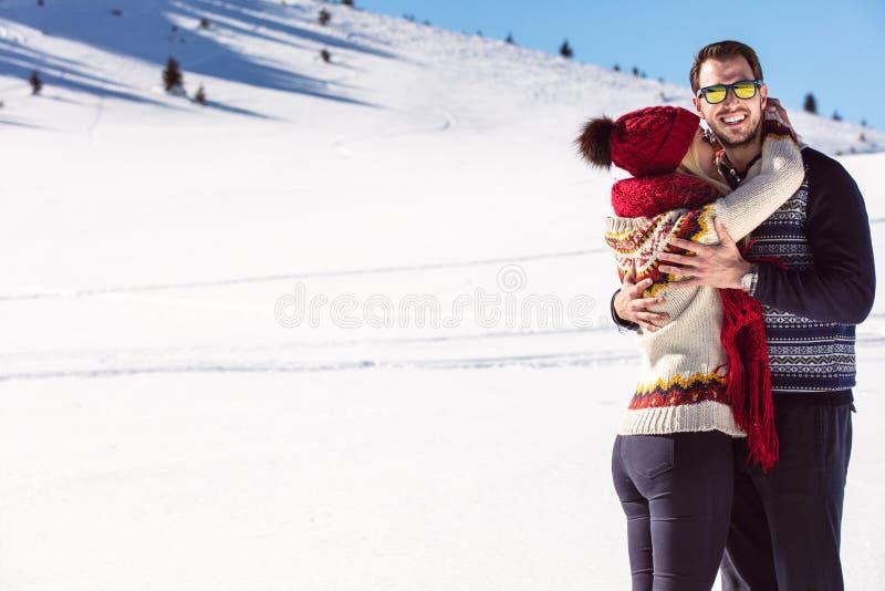 Coppie felici divertendosi sulla montagna della neve fotografia stock