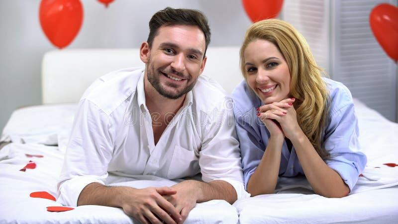 Coppie felici divertenti che riposano sul letto e che sorridono alla macchina fotografica, godente insieme del tempo immagine stock
