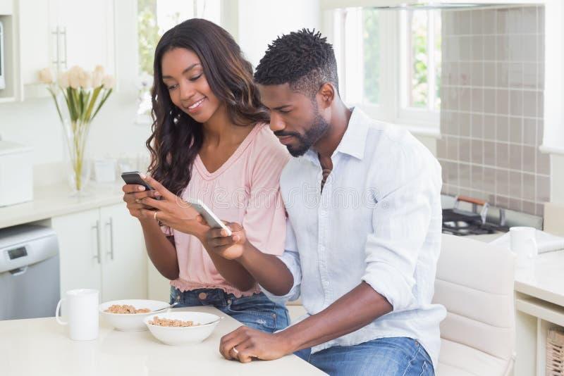 Coppie felici facendo uso dei loro telefoni alla prima colazione fotografia stock
