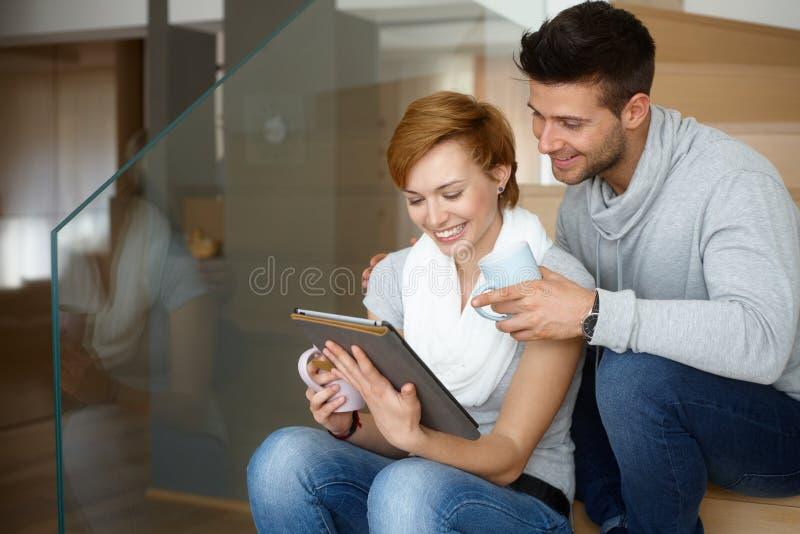Coppie felici facendo uso della compressa a casa fotografia stock libera da diritti