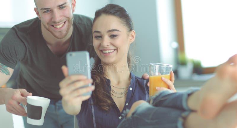 Coppie felici facendo uso dello smartphone che si siede nella cucina immagini stock libere da diritti