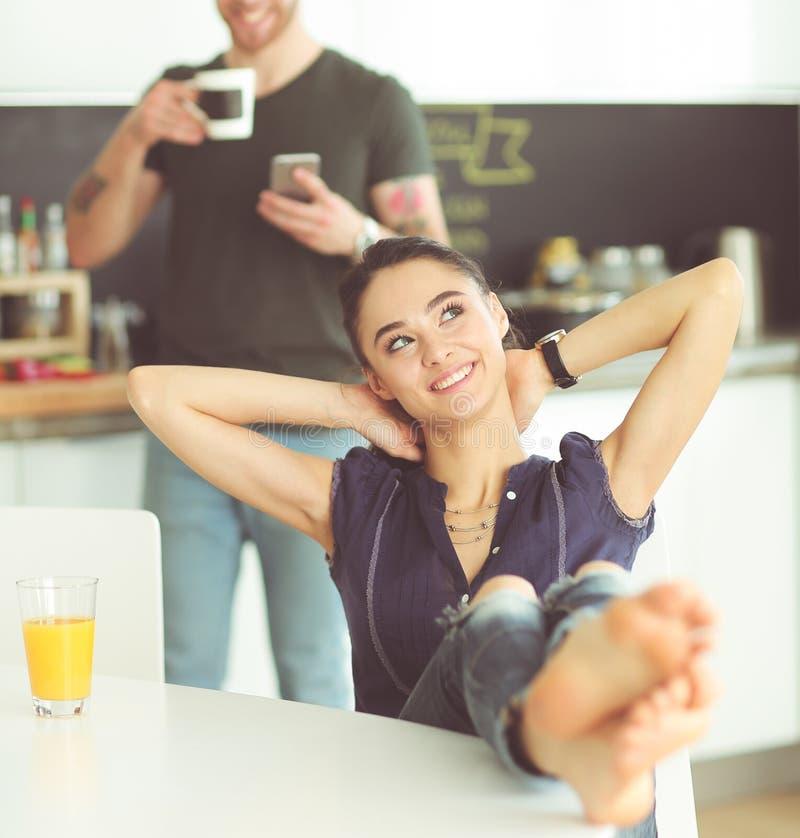 Coppie felici facendo uso dello smartphone che si siede nella cucina fotografie stock