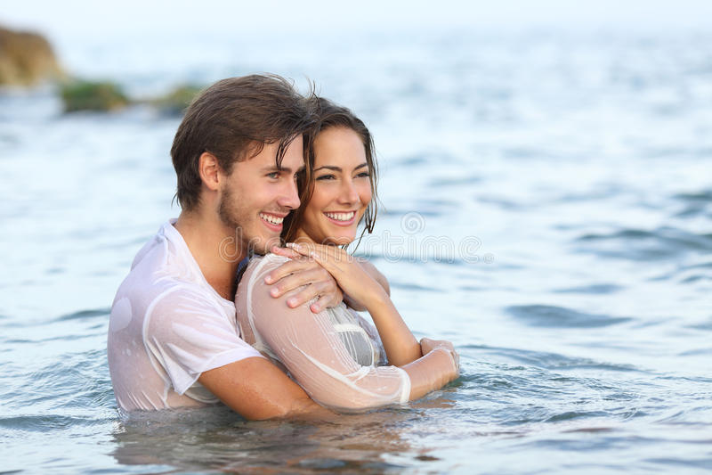 Coppie felici nell'amore che abbraccia e che bagna nella spiaggia immagini stock
