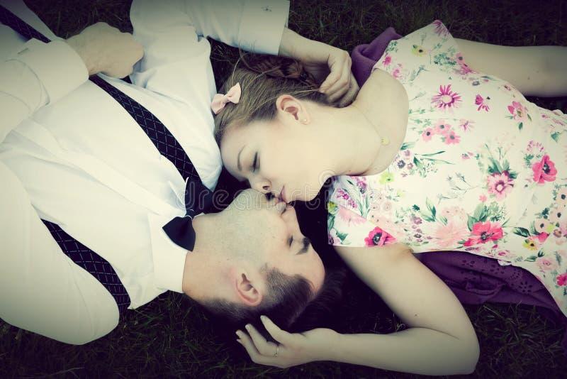 Coppie felici nell'amore che bacia mentre trovandosi sull'erba di estate immagini stock libere da diritti