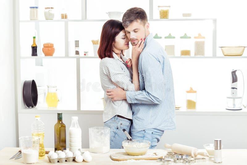 Coppie felici nell'amore che cucina pasta e che bacia nella cucina immagini stock libere da diritti