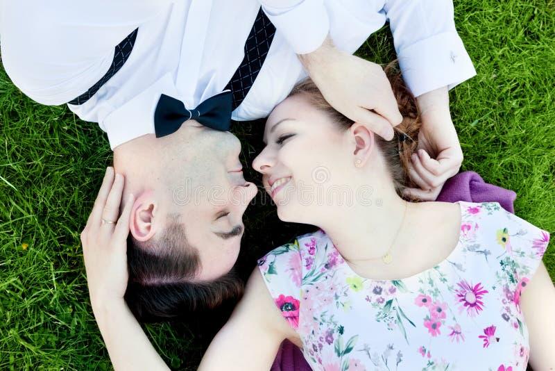 Coppie felici nell'amore che flirta mentre trovandosi sull'erba di estate fotografia stock