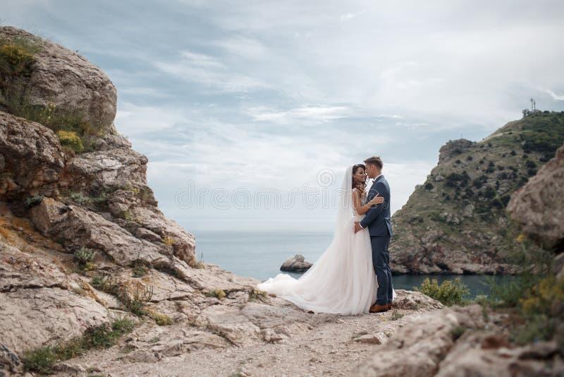 Coppie felici nell'amore con lo sposo e la sposa contro lo sfondo delle montagne vicino all'oceano blu immagine stock libera da diritti