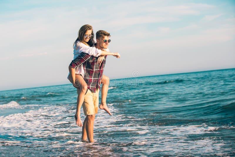 Coppie felici nell'amore sulle vacanze estive della spiaggia fotografia stock libera da diritti