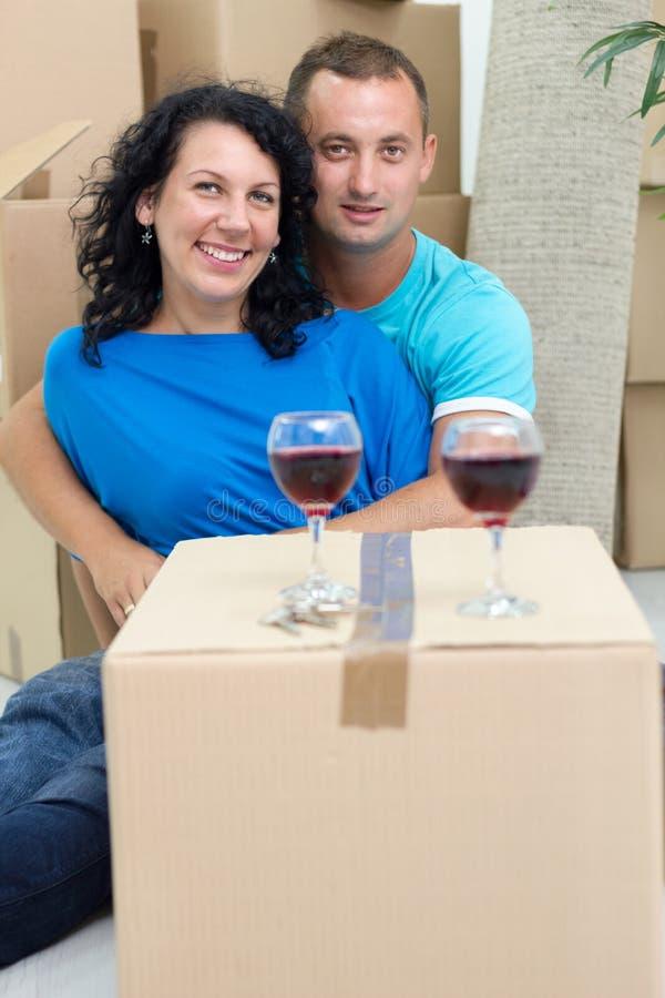 Coppie felici nella loro nuova casa con le scatole di cartone intorno fotografia stock