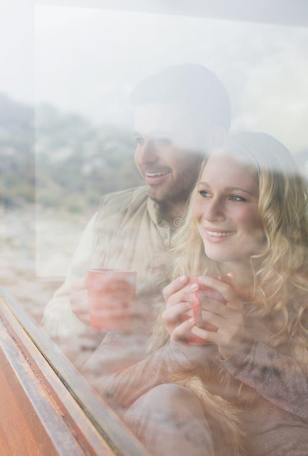 Coppie felici premurose con le tazze di caffè che guardano attraverso la finestra fotografie stock