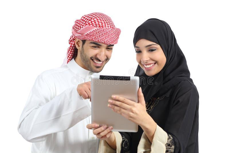Coppie felici saudite arabe che passano in rassegna un lettore della compressa immagine stock libera da diritti