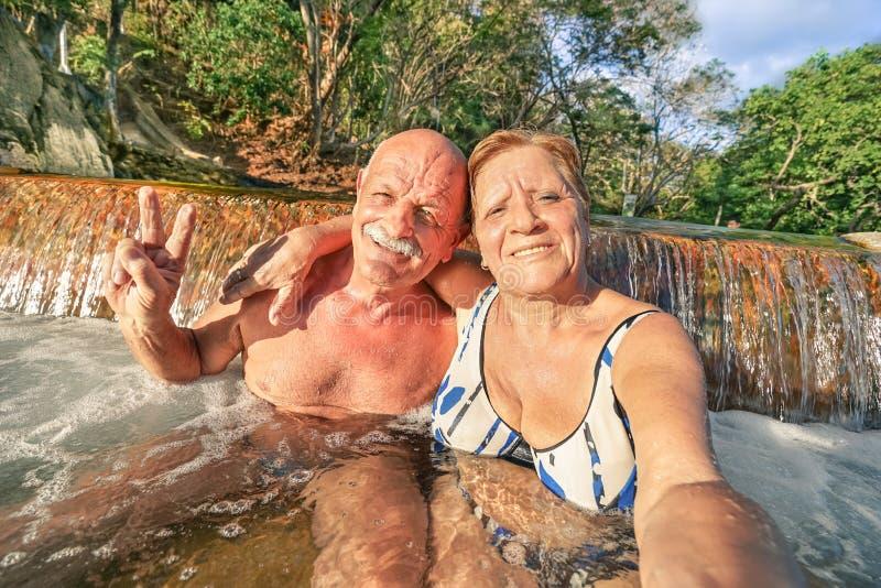 Coppie felici senior che prendono selfie alla sorgente di acqua calda di Maquinit - Coron immagini stock