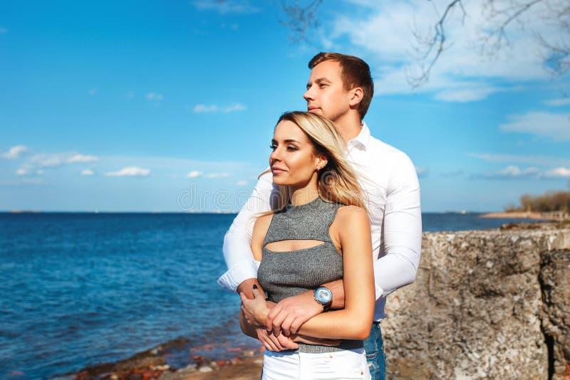 Coppie felici sul fondo del mare Giovani coppie felici che ridono e che abbracciano sulla spiaggia fotografia stock libera da diritti