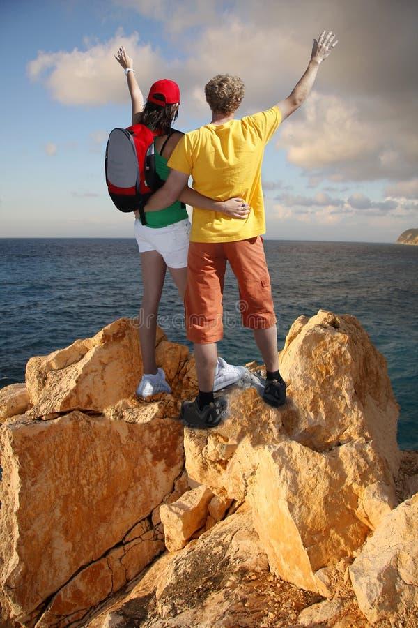 Coppie felici sulla roccia contro il mare immagine stock