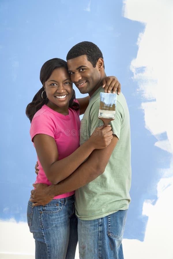 Coppie felici vicino alla parete metà-verniciata. immagine stock libera da diritti