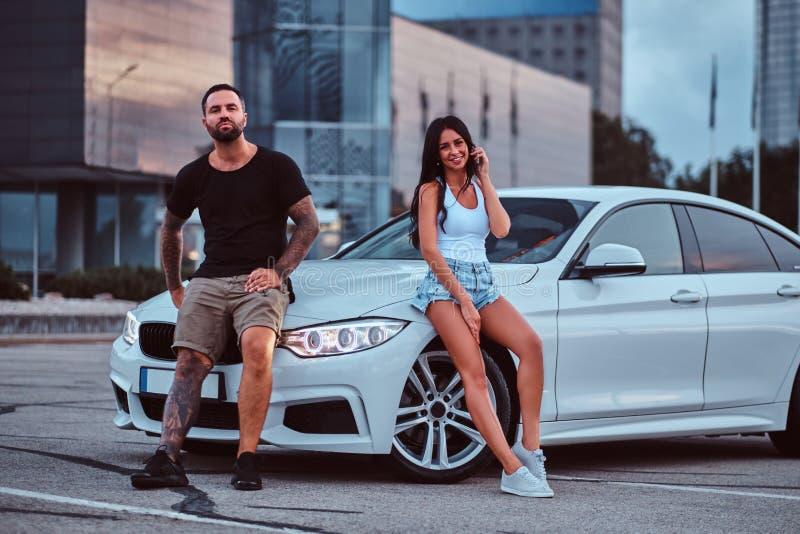 Coppie fresche - ragazza maschio e sensuale tatuata brutale che si appoggia un'automobile di lusso all'aperto contro il grattacie fotografia stock