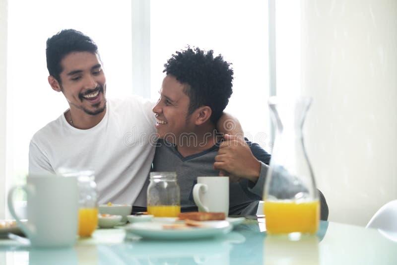 Coppie gay che mangiano prima colazione a casa di mattina immagine stock