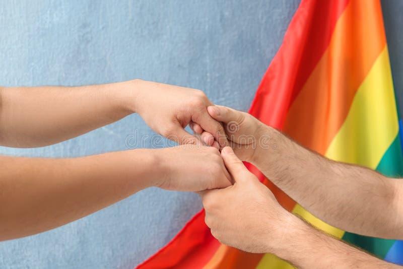 Coppie gay che si tengono per mano vicino alla bandiera fotografia stock