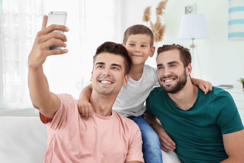 Coppie gay maschii con il figlio adottivo che prende selfie fotografia stock libera da diritti