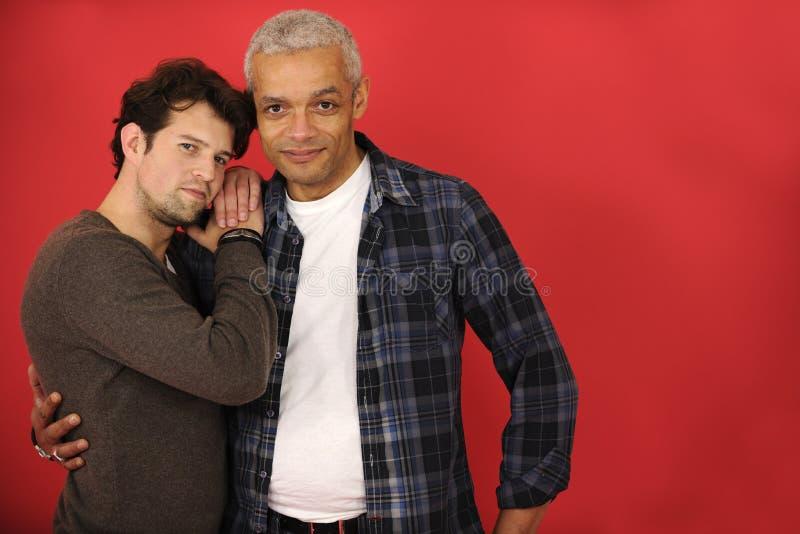 Coppie gay multietniche su fondo rosso fotografia stock libera da diritti