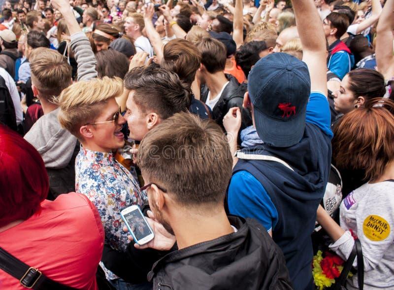 Coppie gay non identificate che stringono a sé durante la parata di gay pride fotografia stock libera da diritti