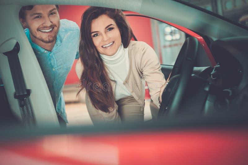 Coppie giovani belle che esaminano una nuova automobile la sala d'esposizione di gestione commerciale fotografie stock libere da diritti