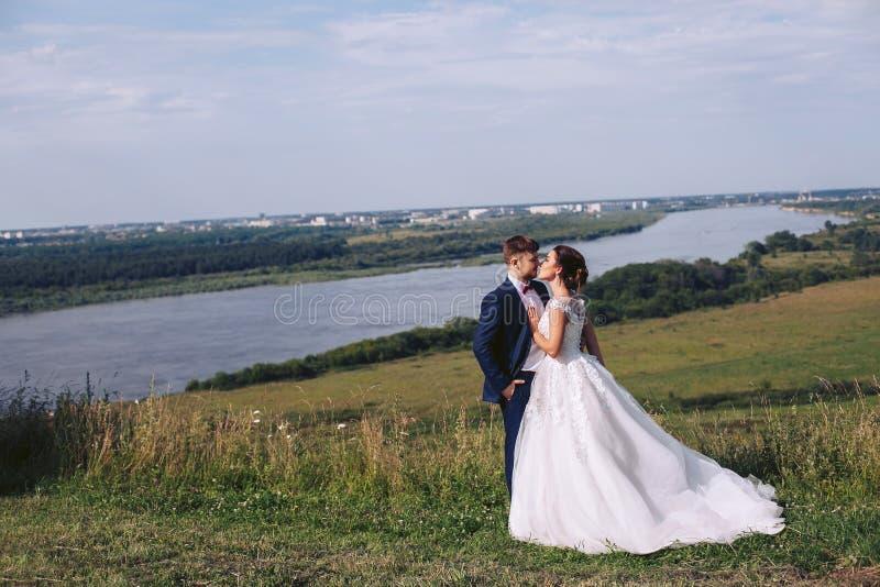 Coppie giovani che baciano all'aperto sul loro giorno delle nozze fotografie stock
