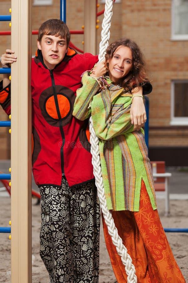 Coppie giovani felici dei pantaloni a vita bassa di modo sul campo da giuoco immagini stock libere da diritti