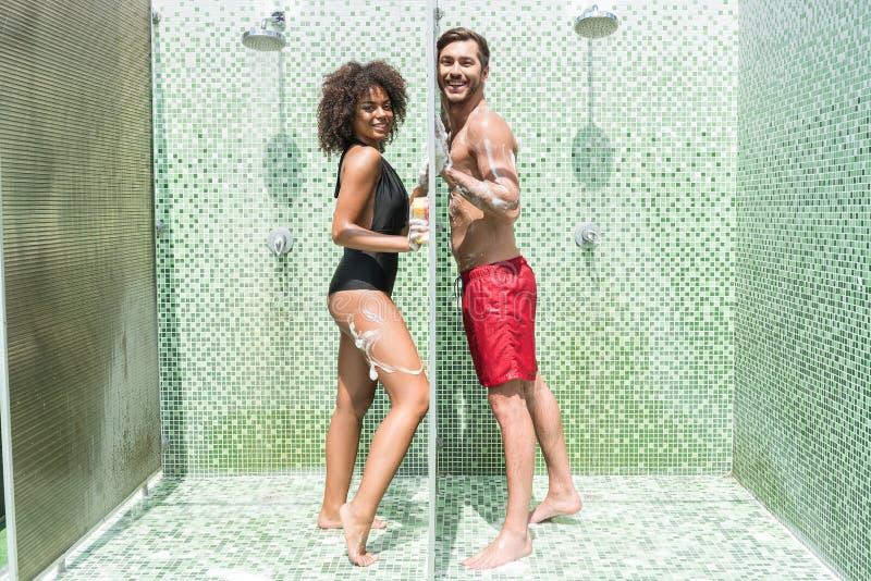 Coppie giovanili di buon umore divertendosi prendendo doccia insieme fotografie stock libere da diritti