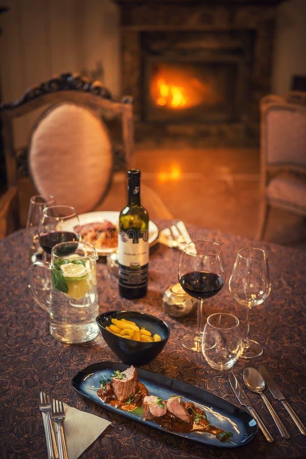 Coppie graziose che bevono vino rosso e che mangiano nel ristorante, orario invernale, cena romantica fotografia stock libera da diritti
