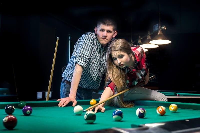 Coppie graziose che giocano biliardo, uomo che si occupa della donna fotografie stock