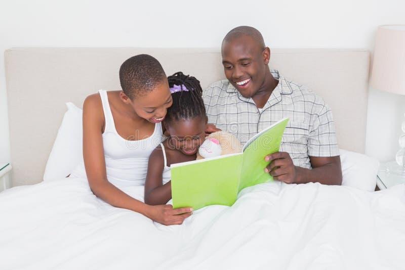 Coppie graziose con sua figlia che legge un Libro verde a letto fotografie stock libere da diritti