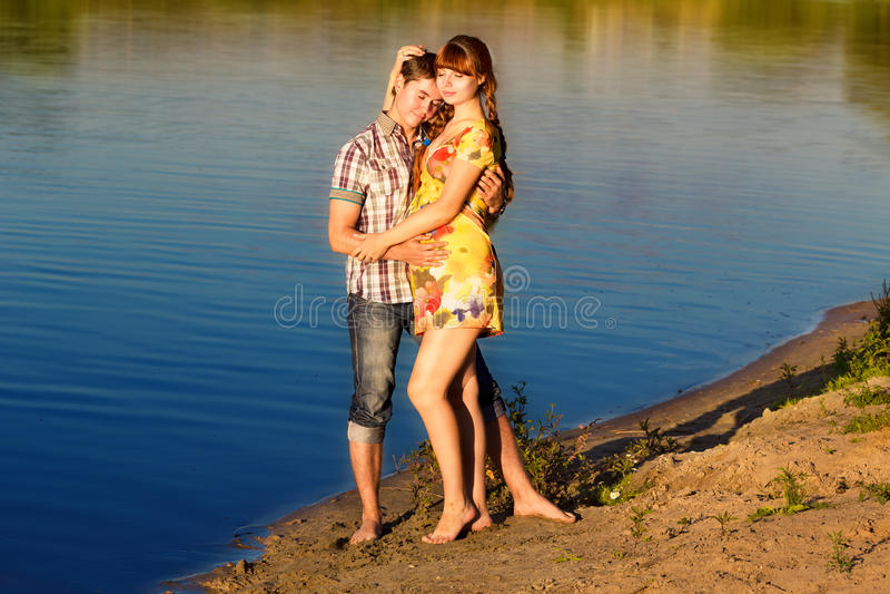 Coppie incinte dei giovani e felici divertendosi sulla spiaggia al sunse fotografia stock