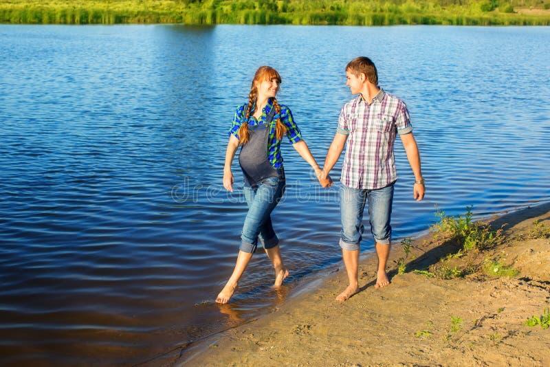 Coppie incinte dei giovani e felici divertendosi sulla spiaggia Estate immagini stock