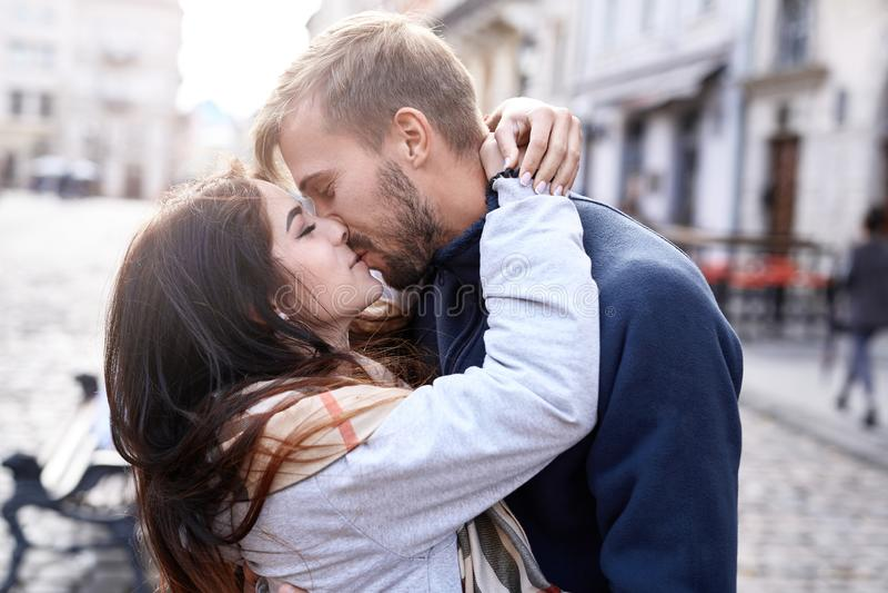 Coppie innamorate che abbracciano e che baciano durante la passeggiata della città immagine stock libera da diritti