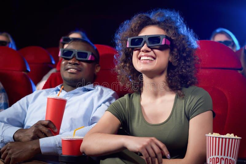 Coppie internazionali felici che mangiano popcorn in cinema fotografia stock