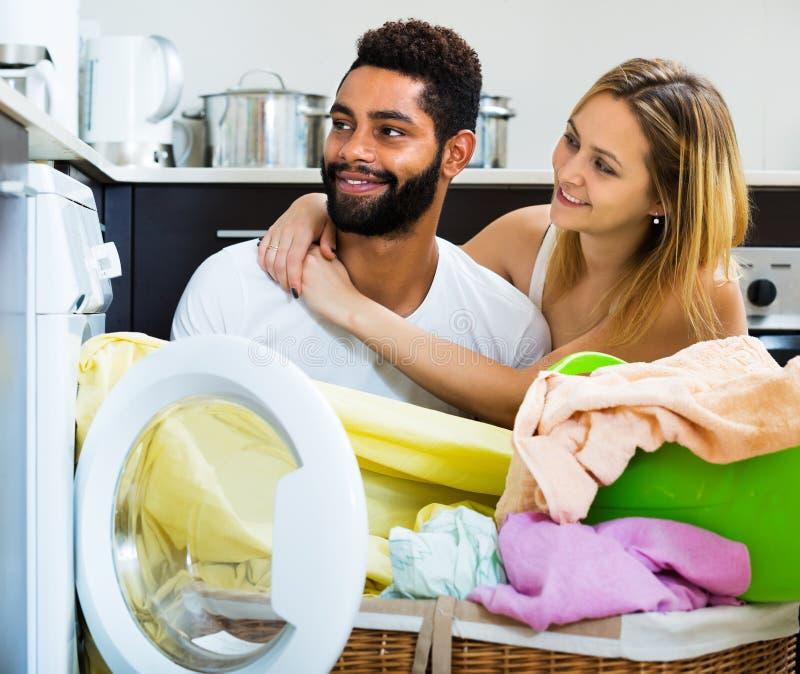 Coppie interrazziali facendo uso della lavatrice fotografia stock