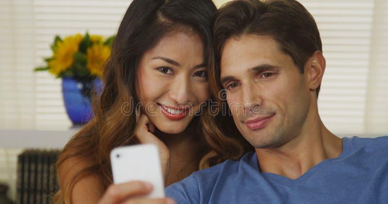 Coppie interrazziali felici che prendono i selfies fotografia stock