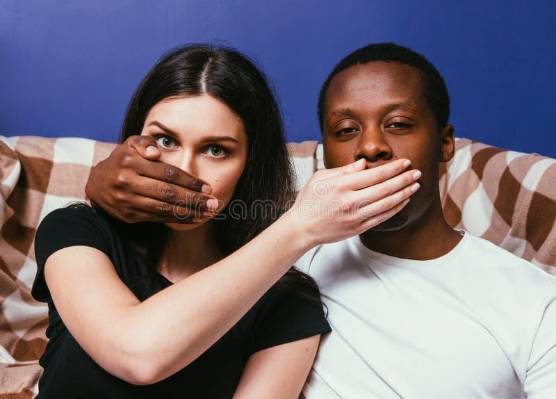 Coppie interrazziali, uomo e donna non dire segreto immagini stock libere da diritti