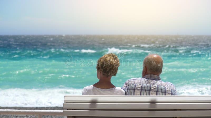 Coppie invecchiate che si siedono sul banco dal lungomare, affrontante mare mosso, viaggio di pensionamento immagini stock