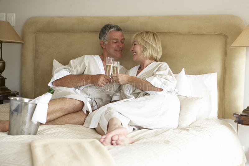 coppie invecchiate del champagne della camera da letto che godono della metà fotografie stock libere da diritti
